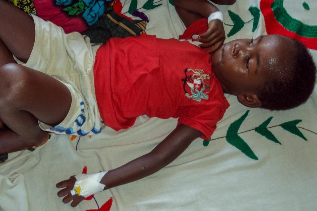 Kind mit Malaria liegt im Bett