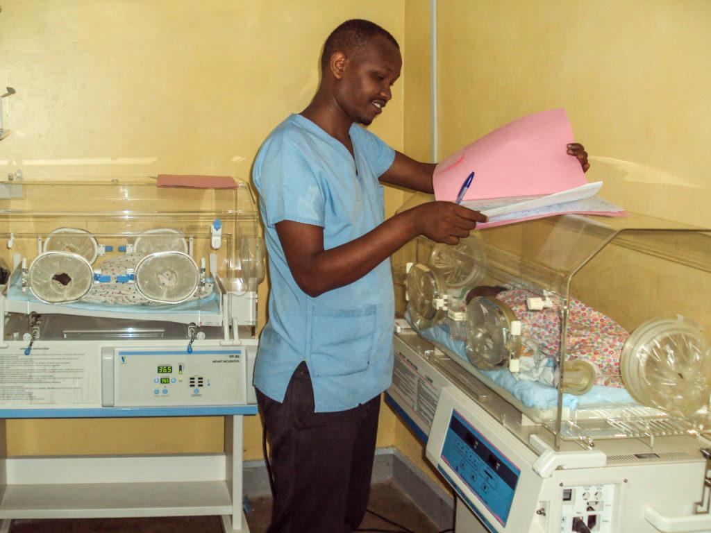 Pfleger steht bei Brutkasten mit Baby